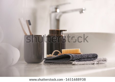 Toiletries on light countertop in light bathroom, closeup Royalty-Free Stock Photo #1651688938