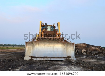 Dozer with bucket for pool excavation and utility trenching. Bulldozer during land clearing and foundation digging at construction site. Earth-moving equipment background #1651696720