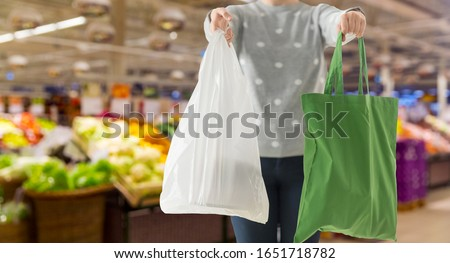consumerism and eco friendly concept - woman holding reusable canvas tote for food shopping and plastic bag over supermarket on background #1651718782