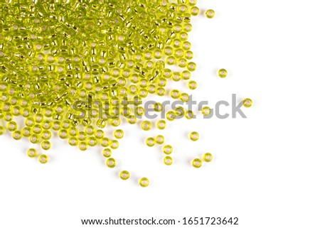 Yellow beads scattered beads on a white background, top view, costume jewelry #1651723642