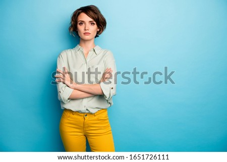 Photo of nice attractive business lady short hairstyle not smiling serious responsible person arms crossed wear casual green shirt yellow pants isolated blue color background #1651726111