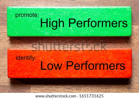 green block with text: promote: High Performersred block with text: identify: Low PerfomersThe background is a dark wooden table Royalty-Free Stock Photo #1651731625
