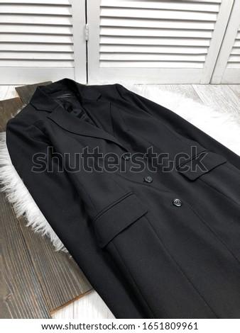 Black women coat on white fur on wooden background #1651809961