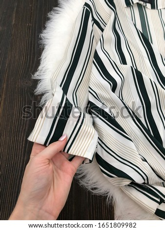 Fabric striped chiffon blouse close-up on a wooden background #1651809982