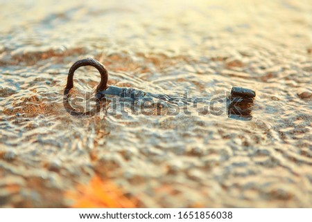 The waves carried the ancient key to the sandy shore. #1651856038