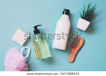 Organic liquid soap, natural coconut shampoo, pink sponge, aloe vera and wooden comb on a green background. Flat lay bath products, toiletries essentials for skin and hair care Royalty-Free Stock Photo #1651888414