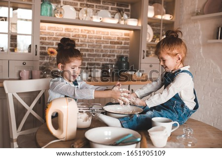 Cute little girls 3 and 6 year old cooking cake with hands in flour in kitchen. Sitting on wooden table. Making dessert together. Childhood.  #1651905109