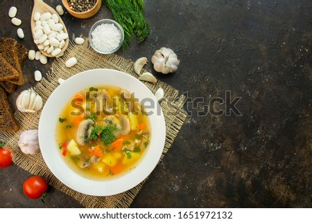 Soup with mushrooms and herbs on a dark background. Vegetarian dish. Hot dish. Copy space. #1651972132
