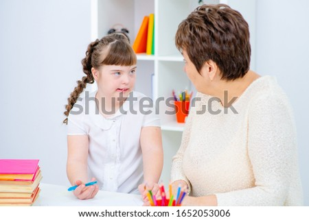 A girl with down syndrome draws at home next to the teacher. #1652053006