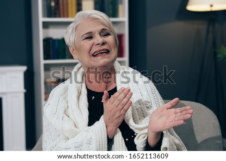 Charming Elderly Lady With Gray Hair Laughs Joyfully And Applauds While Sitting In An Armchair. Floor Lamp, Fireplace And Bookcase On A Blurred Background. Toned Image #1652113609