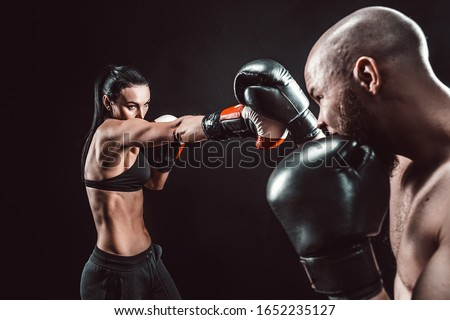 Shirtless Woman exercising with trainer at boxing and self defense lesson, studio, dark background. Female and male fight. Royalty-Free Stock Photo #1652235127