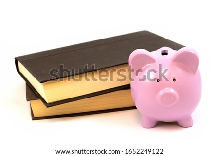 An isolated set of books and a piggy bank. #1652249122