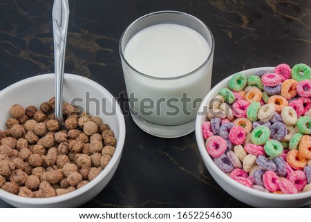 Fruit cereal and chocolate cereal in white cups next to glass of milk in minimalist black table #1652254630