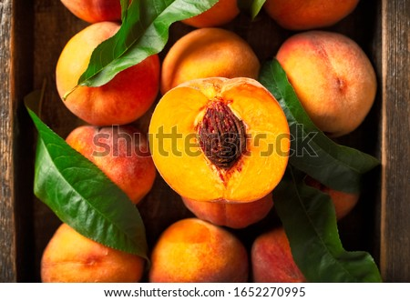 Peaches with leaves in a wooden box with peach in halves on top. Flat lay composition with ripe juicy peaches. Harvest of peaches for food or juice. Top view fresh organic fruit, vegan food. #1652270995