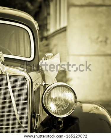 Detail of old timer car detail with wedding decorations in sepia with vignette effect #165229892