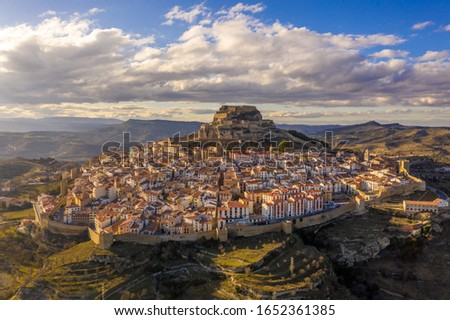 Aerial panoramic view of medieval walled Morella hilltop rampart and castle with blue sky in Spain #1652361385