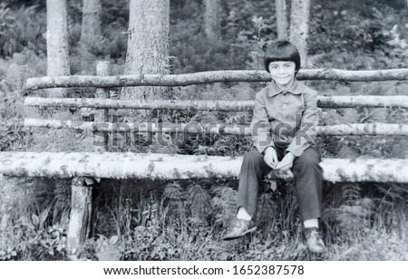 USSR, WESTERN UKRAINE - CIRCA 1982: Vintage photo of little boy Sergey Tsyukevitch sitting on wooden bench in forest in Western Ukraine, USSR #1652387578