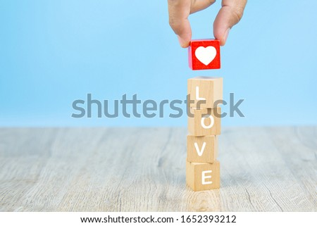 Hand choose a heart shaped icon with a wooden toy block with love texts for Valentine's Day 14. #1652393212