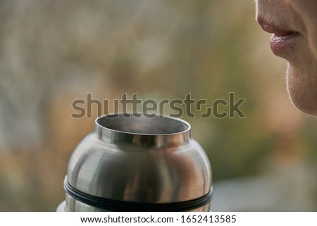 Young woman holds a thermos and drinks tea in autumn forest. Royalty-Free Stock Photo #1652413585