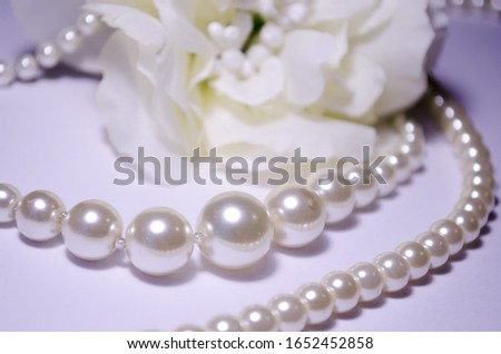 White pearl jewelry. Luxury jewelry for women and girls. Pearl necklace. Artificial pearls. Snow-white pearls on a white background. Bijouterie. Against the background of a peony a pearl necklace. #1652452858