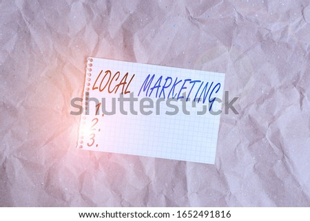Text sign showing Local Marketing. Conceptual photo targets customers by finely grained location such as a city Papercraft craft paper desk square spiral notebook office study supplies. #1652491816