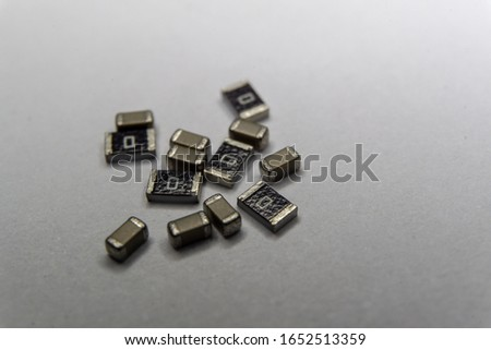 Abstract close-up of grey scattered 0603 SMT surface mount chip MLCC capacitors and 1206 resistors power electronics components on white background in random pattern #1652513359