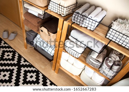 Spring cleaning of closet. Vertical tidying up storage. Neatly folded bed sheets in the metal black baskets for wardrobe. Nordic style. #1652667283