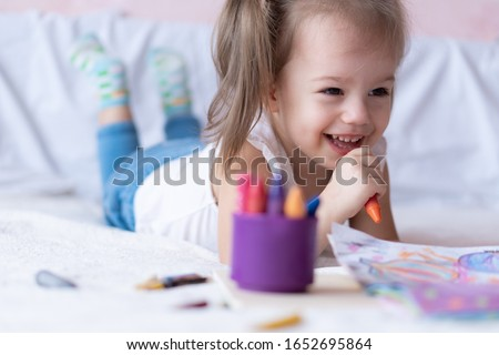 Beautiful girl draws with pencils in bed. Little girl two years paints coloring book lying on the bed. Little baby with a ponytail smiling while lying on the bed. Pretty girl paints with pencils and