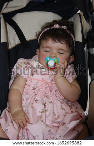 Italy, Milan - May 24, 2009: 1 year old girl asleep. The tenderness of a little girl who sleeps peacefully and has sweet dreams lying in the stroller on a spring afternoon. #1652695882