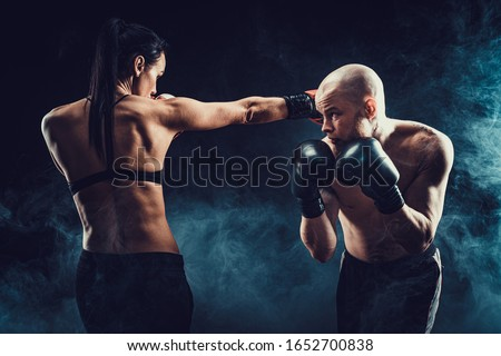 Shirtless Woman exercising with trainer at boxing and self defense lesson, studio, dark background. Female and male fight. Royalty-Free Stock Photo #1652700838