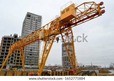 High heavy yellow metal iron load-bearing construction stationary industrial powerful gantry crane of bridge type on supports for lifting cargo on a modern construction site of buildings and houses. #1652771884