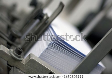 a pile of white paper envelopes in printing machine ready for printing Royalty-Free Stock Photo #1652803999