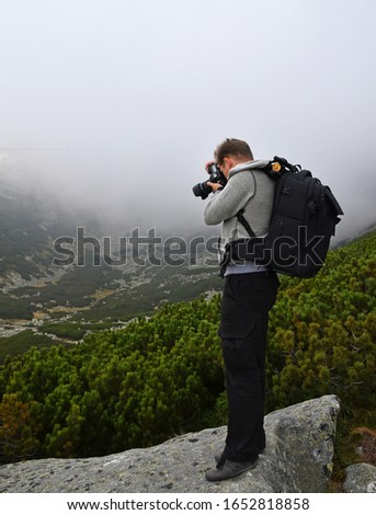 One young tourist man photographer with backpack taking pictures in mountains on foggy weather day, low angle rear side view