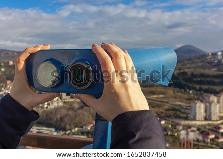 Female hands hold sightseeing touristic telescope. View from the observation deck (viewing platform) at the mountains landscape. Tourist walk, excursion. Copy space for text. #1652837458