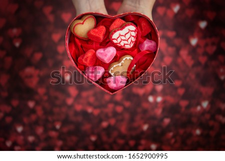 heart-shaped box, with heart-shaped jelly beans, heart-shaped cookies and red background #1652900995