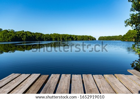 A beautiful shot of a calm lake with a clear blue sky in the background #1652919010