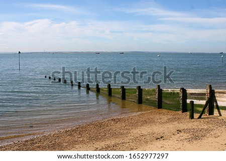 A wooden breakwater, a barrier built out into the sea to protect a coast or harbour from the force of waves, jutting into the North Sea off the coast of Southend-on-Sea.  Image has copy space. #1652977297