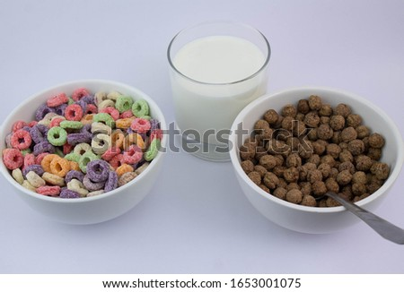 Fruit cereal and chocolate cereal in white cups next to glass of milk in minimalist black table #1653001075