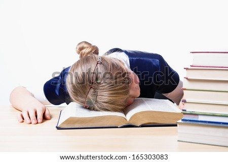 Exhausted girl sleeping on a book after studying. #165303083