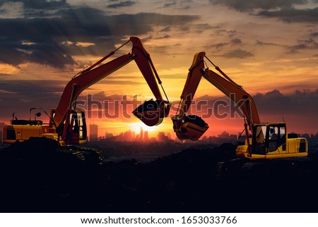 Two Excavators are digging the soil in the construction site on the sky sunset with cityscapes background #1653033766