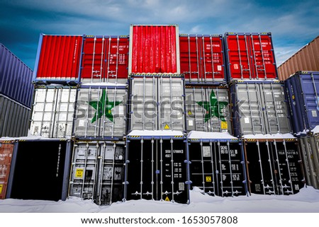 The national flag of Syria on a large number of metal containers for storing goods stacked in rows on top of each other. Conception of storage of goods by importers, exporters