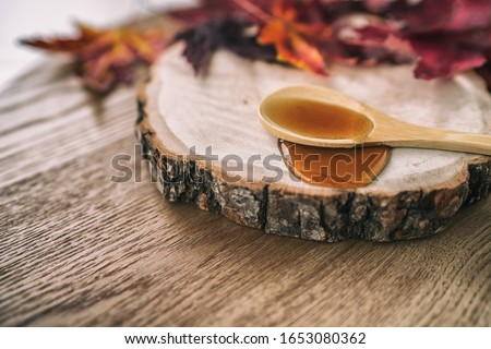Maple syrup sugar liquid in wooden spoon from Quebec restaurant sugar shack called Cabane a sucre maple trees sap farm. Canadian delicacy sweet dessert ingredient, Royalty-Free Stock Photo #1653080362