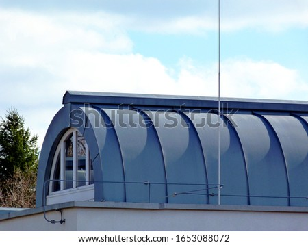 curved dome shaped zink plate covered skylight with circular white window on flat roof with shadows. modern architecture concept. abstract detail. pine tree in the background. bright blue sky. #1653088072