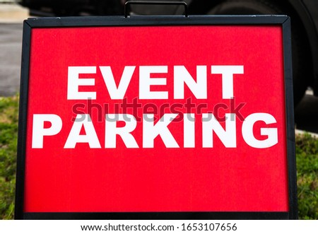 Event parking sign with white lettering and bright red background and a black metal border at ground level