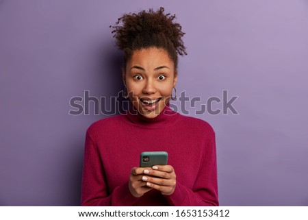 Happy surprised curly haired woman receives good news from friend, holds mobile phone, sends text mesages, wears casual turtleneck, isolated on purple background, downloads app, browses internet #1653153412