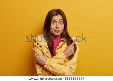 Photo of unaware hesitant woman with dark hair points sideways, chooses between two options, has surprised face expression, wears jacket, poses against yellow background, says better to take look
