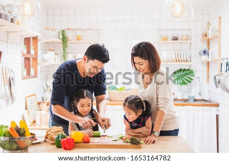 Asian family enjoy playing and cooking food in kitchen at home #1653164782
