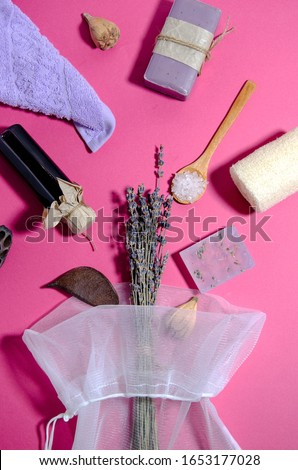 SPA accessories lie on a pink background. Purple towel, lavender oil and soap, salt, loofah washcloth, bag with a bouquet of lavender. Vertical image, flat lay