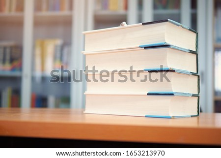 Pile of business books on study desk in library self access learning room, textbooks at school, college, or university, education or academic concept picture related to research, selective focus mode