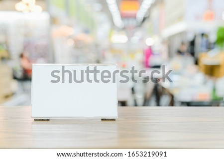 Mockup menu frame on counter bar table , Stand for booklets with advertising promotion recommended menu on blurred interior restaurant or coffee shop background clipping path on acrylic frame